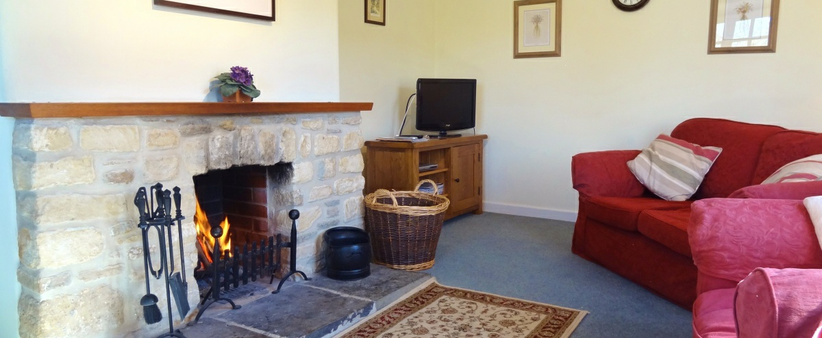 Comfortable sitting room with roaring log fire.